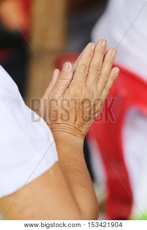 Hand of old people of asian pay respect to the Buddha and Thai monkconcept of faith and good deeds.