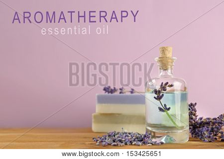 Spa composition with essence and soap, closeup. Text AROMATHERAPY ESSENTIAL OIL on pink background. Spa beauty concept.