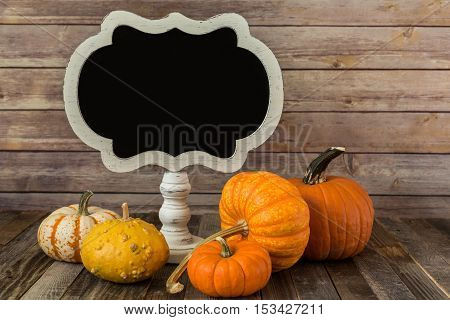 Ornamental gourd with a chalkboard sign on wooden backdrop