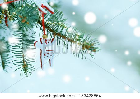 Decorated fir tree branch covered with snow, closeup. Snowy effect, Christmas celebration concept.