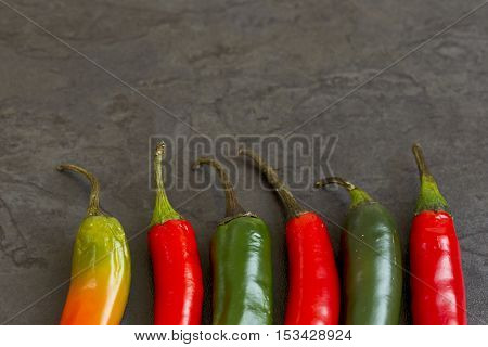 hot redgreen and orange chilies in a row on a dark grey background