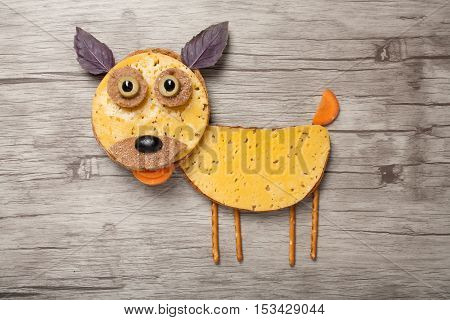 Funny dog made of bread and cheese on board