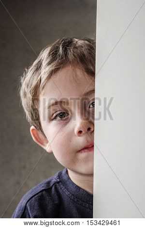 Serious young boy peeking around a wall