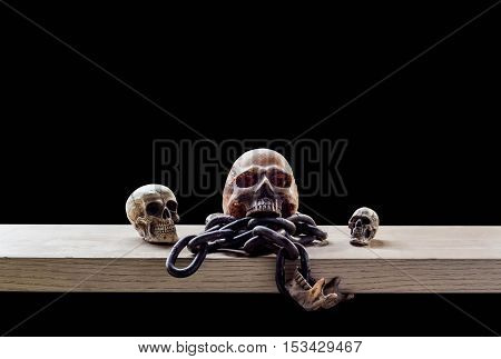 Skulls and chains on a wooden with a black background.