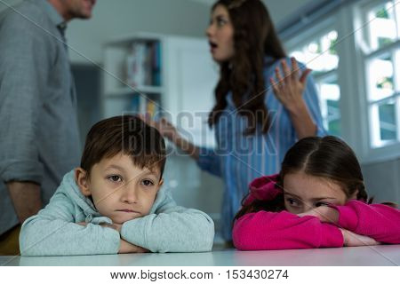 Upset children sitting while couple arguing with each other in the kitchen
