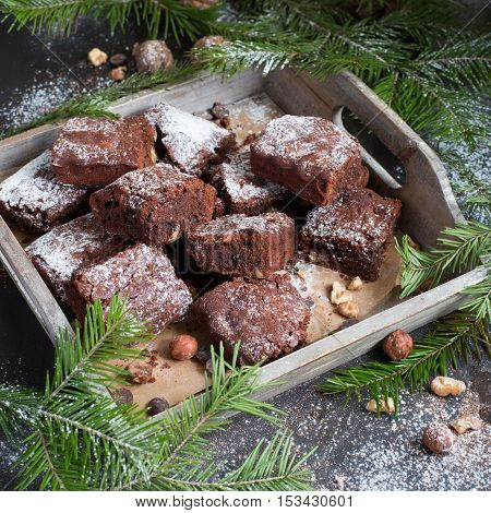 Chocolate cake decorated with strawberries. Brownie. Cake in the shape of a ring, wooden background. Rustic. Food style. Yummy. Sweet idea. Christmas dessert. Christmas tree ornaments. New Year.
