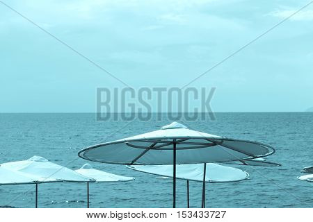 solar umbrellas on the beach and against the background of the sea and the sky of blue tone