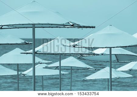 solar umbrellas closeup on the beach and against the background of the sea and the sky of blue tone