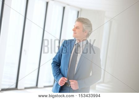 Confident mature businessman looking away in new office