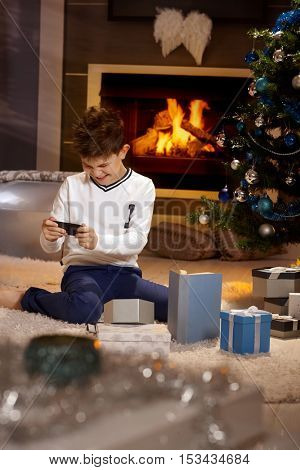Little boy sitting on floor by christmas tree, playing with mobile phone.