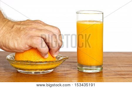 mans hand squeezing half an orange with a glass of fresh orange juice next to it.