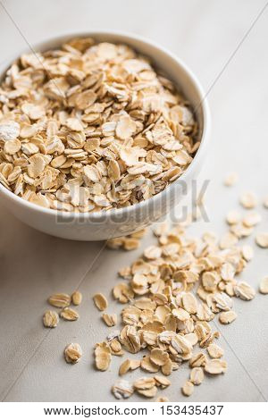 Dry rolled oatmeal in bowl on kitchen table.