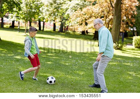 family, generation, game, sport and people concept - happy grandfather and grandson playing football at summer park