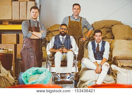 Portrait of handsome colleagues sitting on textile bags of coffee beans and looking at camera
