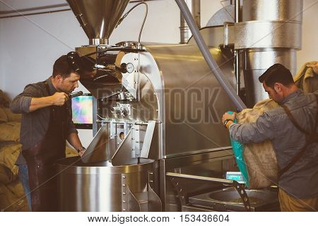 process of preparation roasted coffee.two workers at roasting machine.