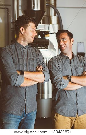 Portrait of two confident smiling coffee makers looking at each other against of roasting machine