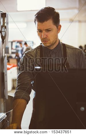Portrait of adult man looking down while working on computer beside coffee roasting machine