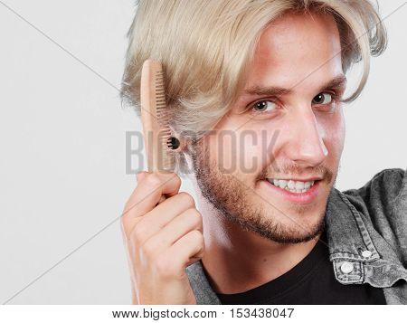 Man With Stylish Haircut Combing His Hair