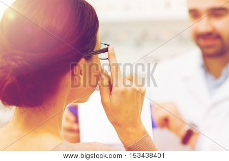 health care, people, eyesight and vision concept - close up of optician and woman choosing glasses at optics store