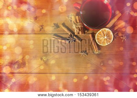 christmas, holidays, cooking and spice concept - close up of tea cup with cinnamon, anise and dried orange on wooden table from top over lights