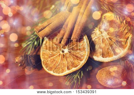 decoration, winter, christmas, holidays and new year concept - close up of christmas fir branch with cinnamon and dried orange over lights