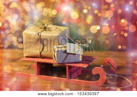 christmas, holidays, presents, new year and celebration concept - close up of gift boxes with blank note on red wooden sleigh over lights background