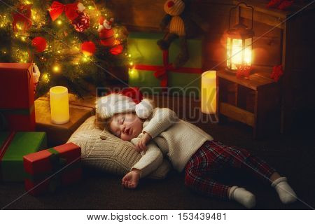 Merry Christmas and Happy Holidays! Cute little child baby girl sleeping near Christmas tree indoors.
