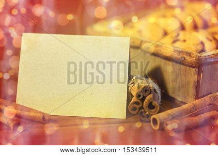 baking, culinary, christmas, holidays and food concept - close up of blank greeting card with oat cookies in wooden box and cinnamon over lights