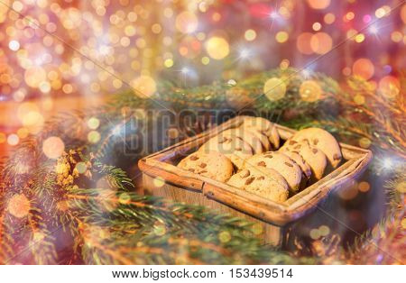 christmas, holidays, food and baking concept - close up of natural green fir christmas wreath and oat cookies in wooden box on table over lights