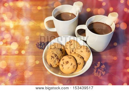 holidays, christmas, winter, food and drinks concept - close up of cups with hot chocolate or cocoa drinks and marshmallow with oat cookies on wooden table over lights