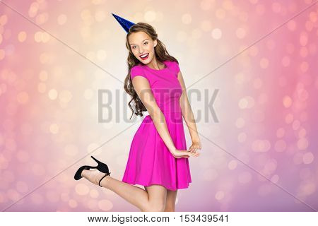 people, holidays, birthday and celebration concept - happy young woman or teen girl in pink dress and party cap over rose quartz and serenity lights background
