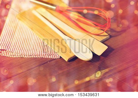 christmas, holidays, baking, cooking and home kitchen concept - close up of kitchenware and towel set on wooden board over lights
