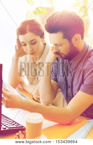 business, startup and people concept - creative team of man and woman with computer and files solving problem in office