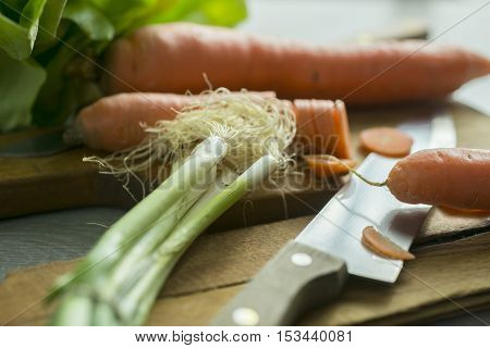 Homemade salad spring onion carrot over cutting board