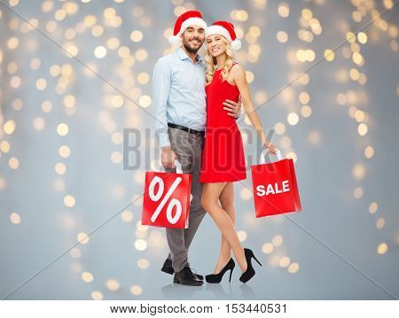 christmas, people, sale, discount and holidays concept - happy couple in santa hats hugging with red shopping bags over lights background