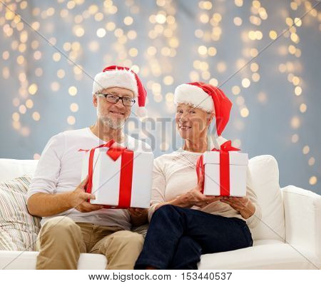 family, holidays, christmas, age and people concept - happy senior couple in santa helper hats with gift boxes over lights background