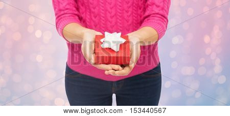 christmas, holidays and people concept - close up of woman in pink sweater holding gift box over rose quartz and serenity lights background