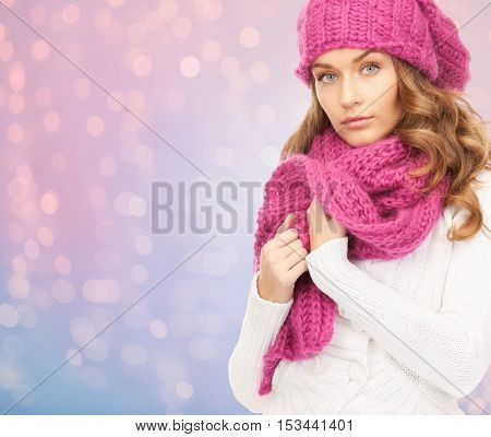 winter holidays, christmas and people concept - close up of young woman in hat and scarf over rose quartz and serenity lights background