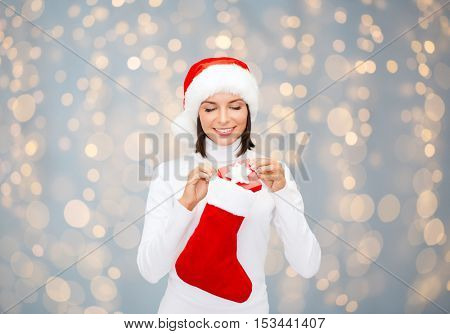 christmas, x-mas, winter holidays and people concept - smiling woman in santa helper hat with small gift box and stocking over lights background