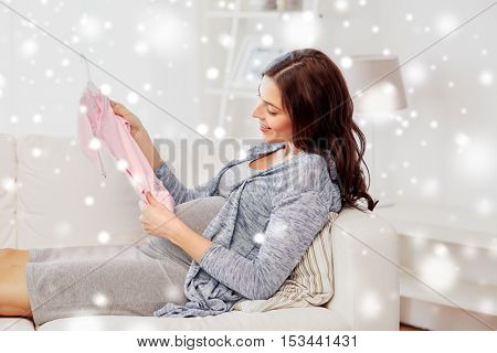 motherhood, pregnancy, winter, people and kids clothing concept - happy woman holding and looking at pink baby girls bodysuit at home over snow