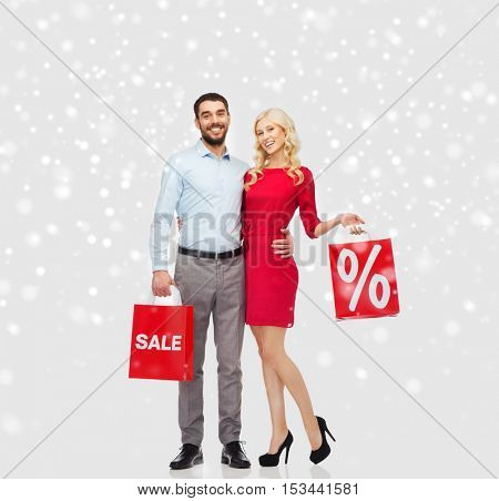 people, sale, christmas, winter and holidays concept - happy couple with red shopping bags hugging over snow background