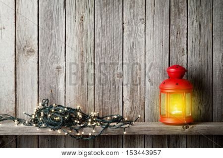 Christmas candle lantern and xmas lights in front of wooden wall. View with copy space for your text