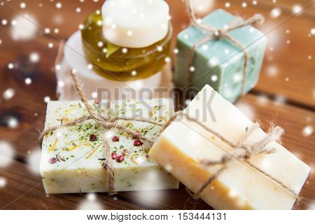 beauty, spa, bodycare, bath and natural cosmetics concept - close up of handmade soap bars on wooden table over snow
