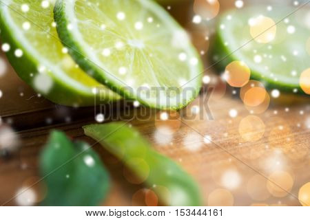 fruits, citrus, detox, diet and objects concept - lime slices on wooden table over lights and snow