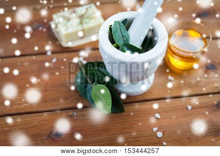 beauty, spa, bodycare, natural cosmetics and wellness concept - mortar and pestle with leaves with leaves on wooden table over snow