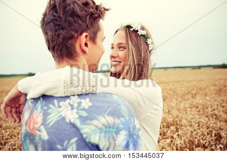 summer holidays, love, romance and people concept - happy smiling young hippie couple hugging outdoors
