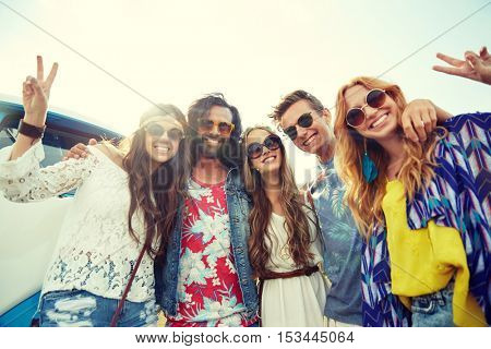 summer holidays, road trip, vacation, travel and people concept - smiling young hippie friends over minivan car showing peace hand sign