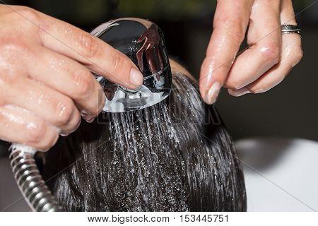 Washing customer hair in a hair salon.