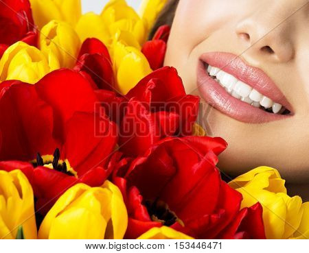 A beautiful  smile of healthy teeth of the young lady. Half face of a pretty happy woman with tulips