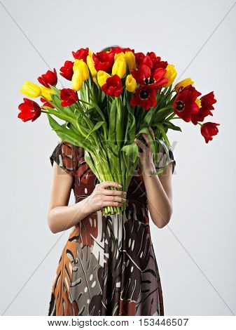 Girl covering her face with big bouquets of flowers